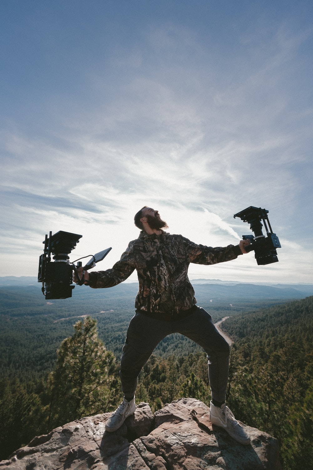 person standing on rocky mountain peak while holding two cameras