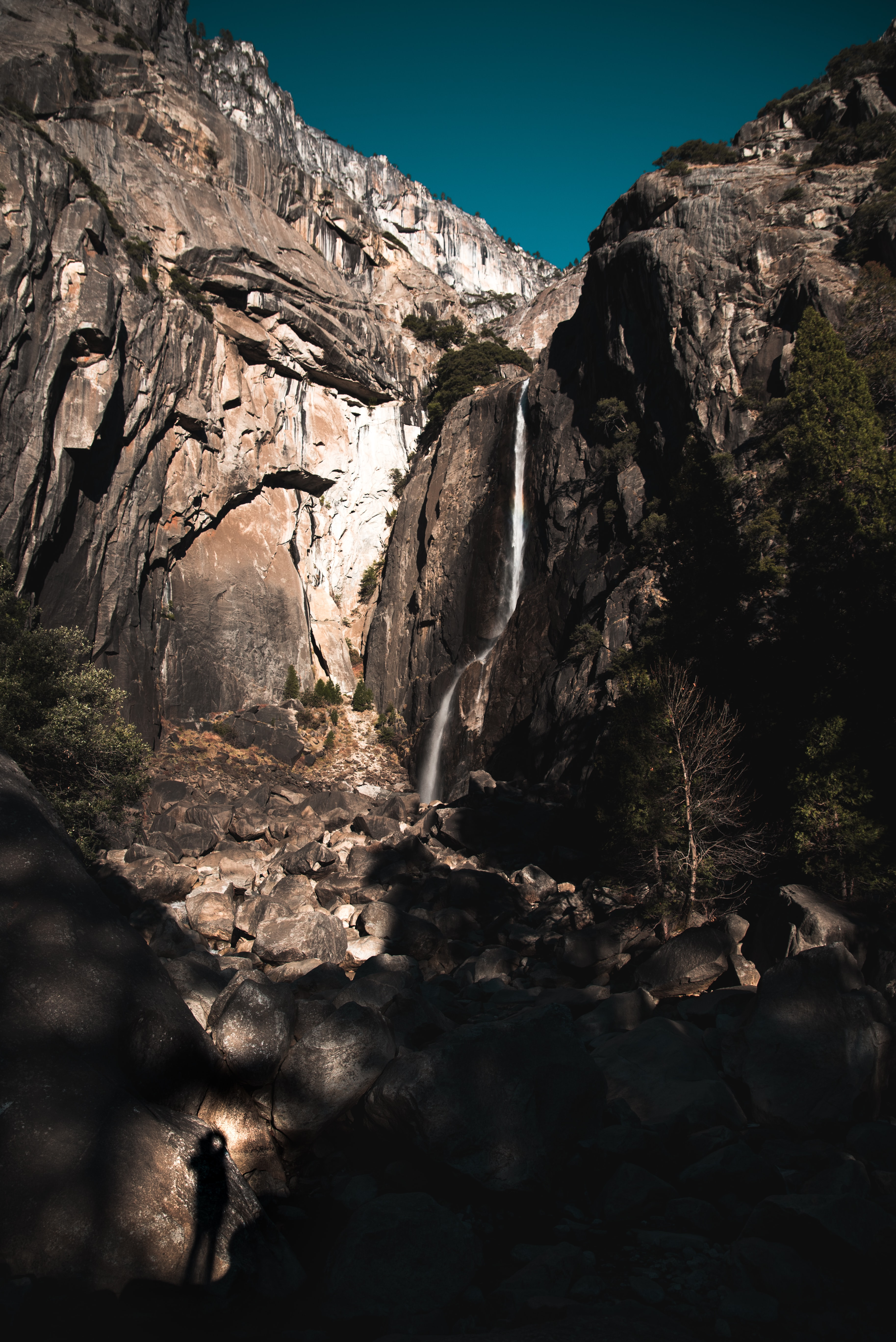 waterfalls surrounded with rock mountain under blue sky during daytime