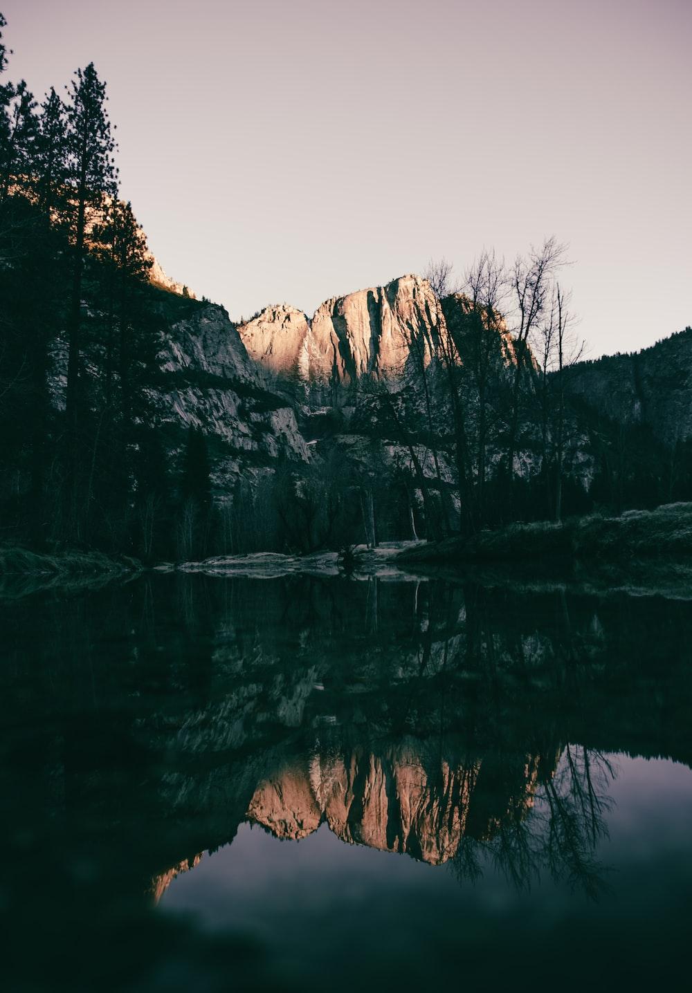 rock mountain across body of water