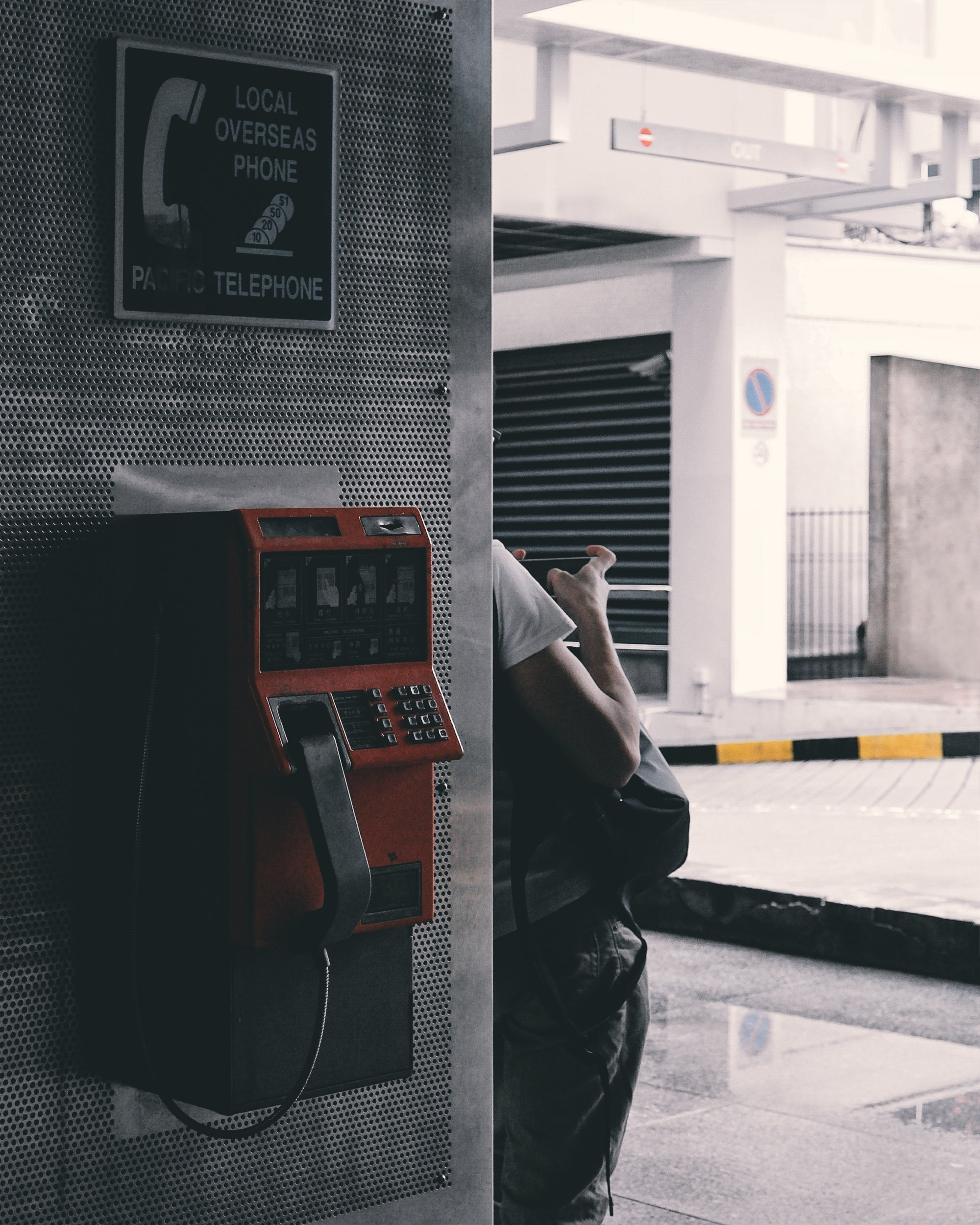 person leaning on wall near brown payphone