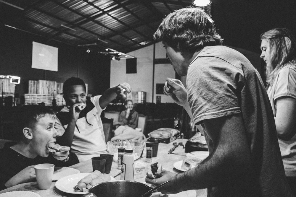 grayscale photography of people eating food