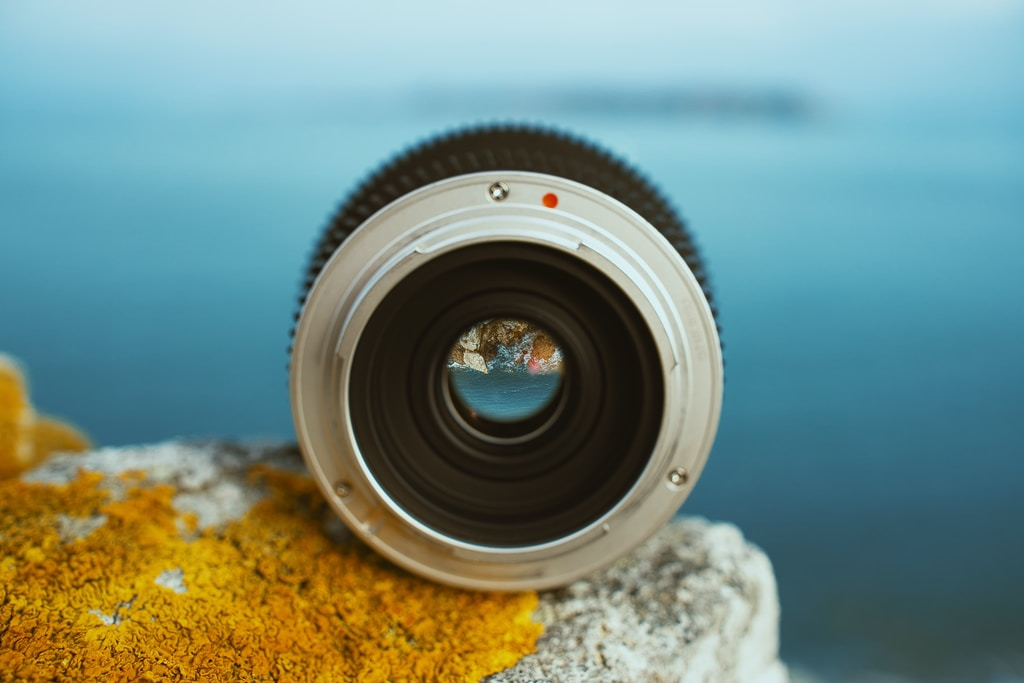 round black and grey camera lens on rock
