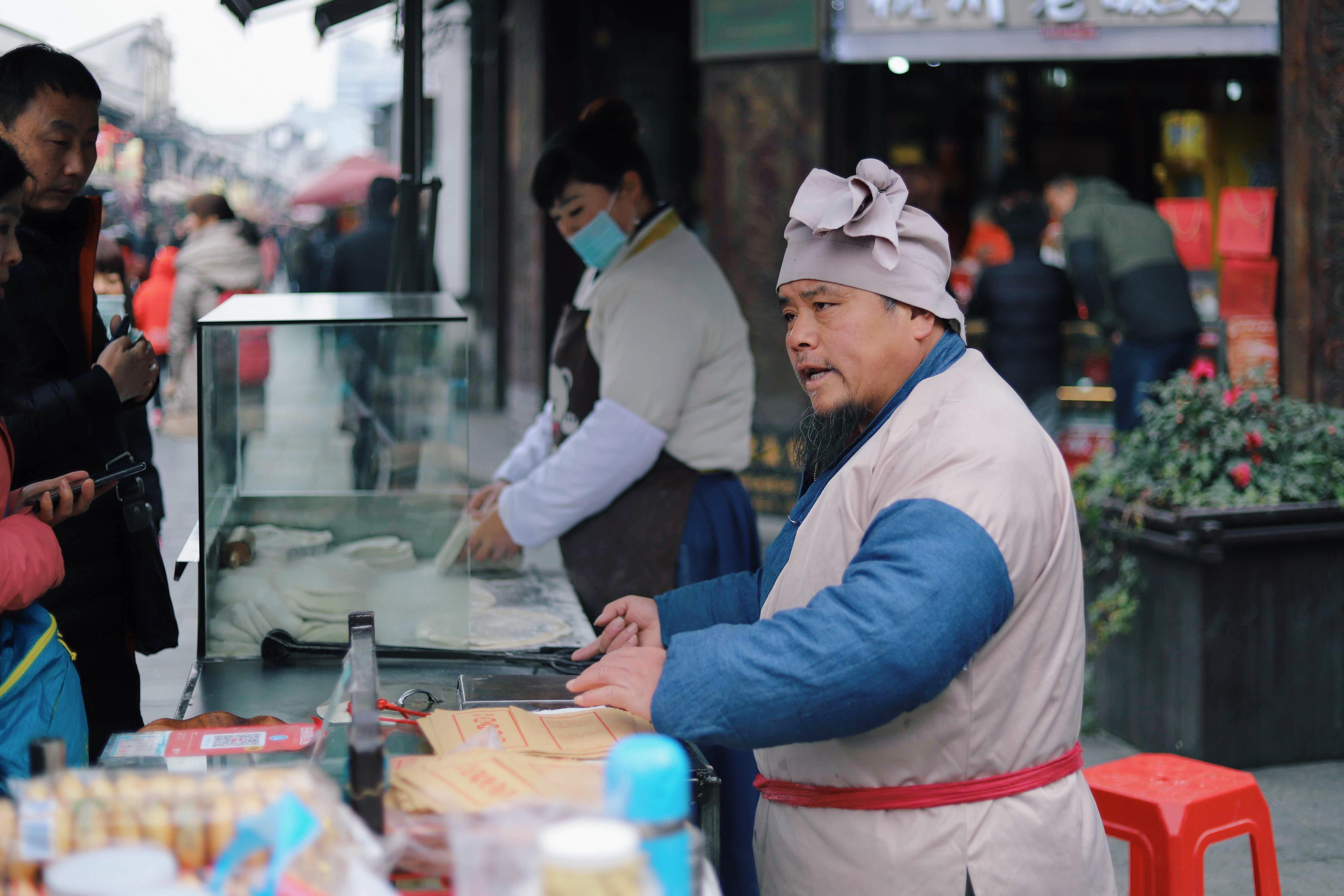 man serving food near red stool