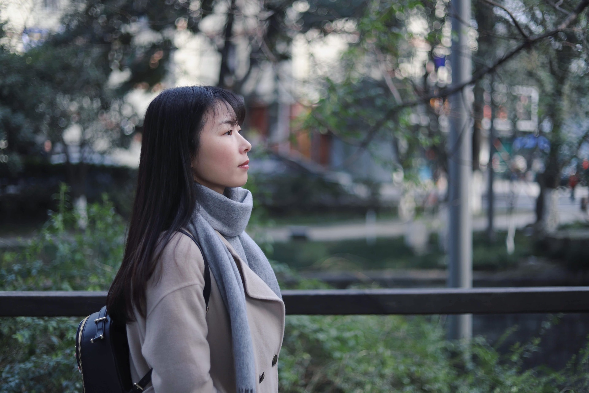 woman in gray scarf and coat standing near bridge
