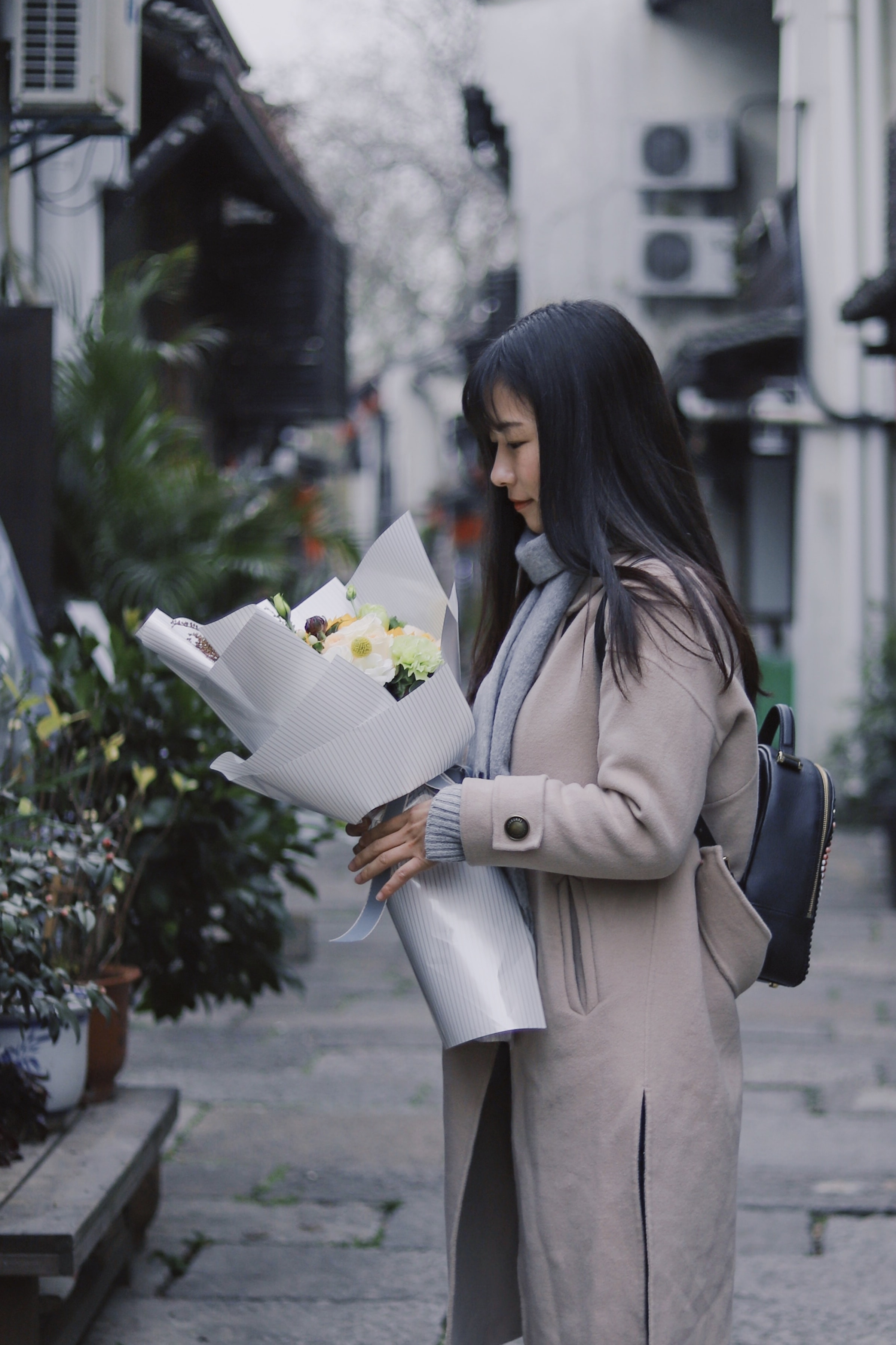 woman holding bouquet of flowers standing near green leaf plant