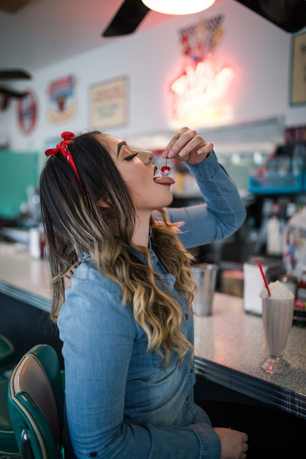 woman wearing blue long-sleeved shirt eating cherry from parfait inside room