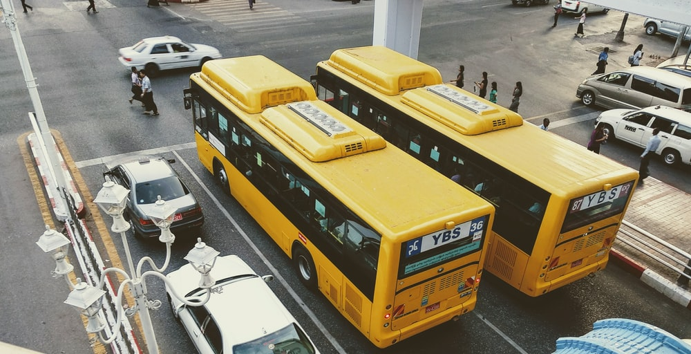 two buses beside white cars