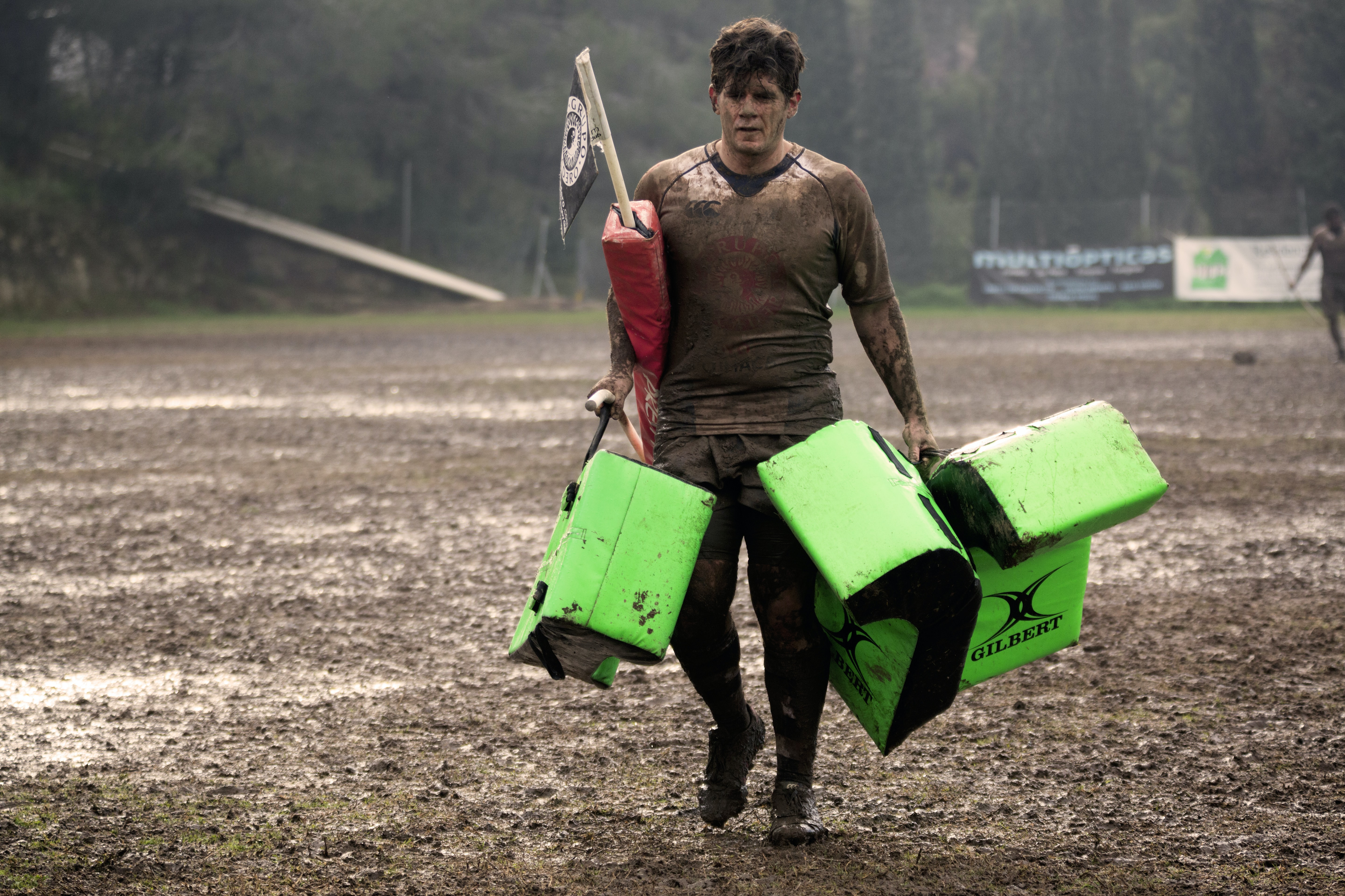 man covered in mud carrying leather training pads