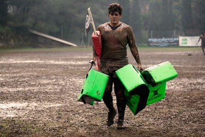 man covered in mud carrying leather training pads rugby teams background