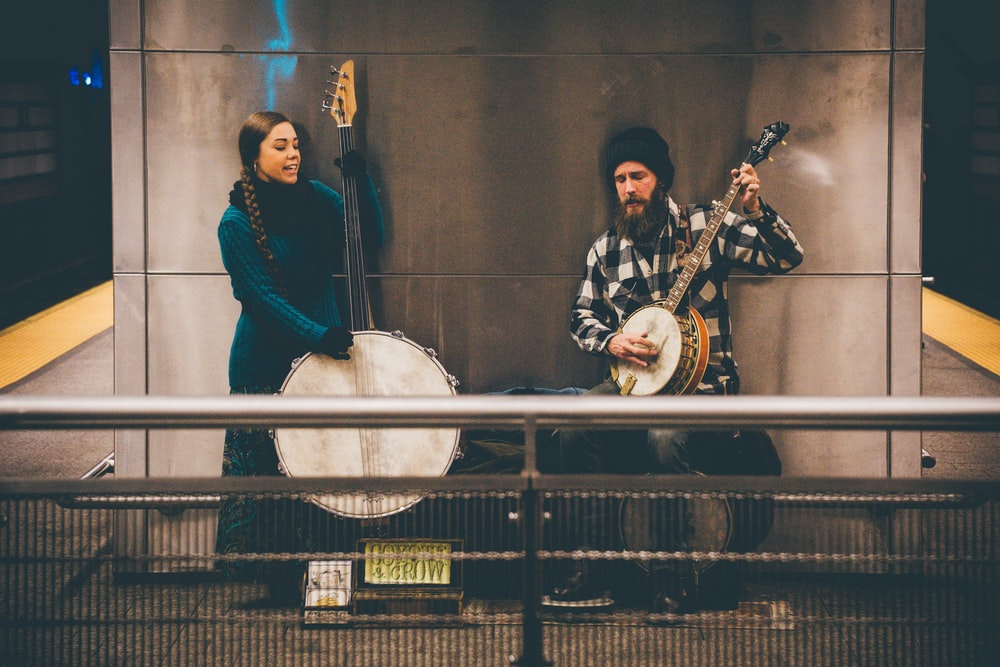 man and woman playing string instruments standing near wall