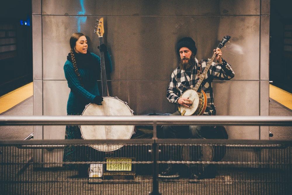 男と女の壁の近くに立っている弦楽器を演奏