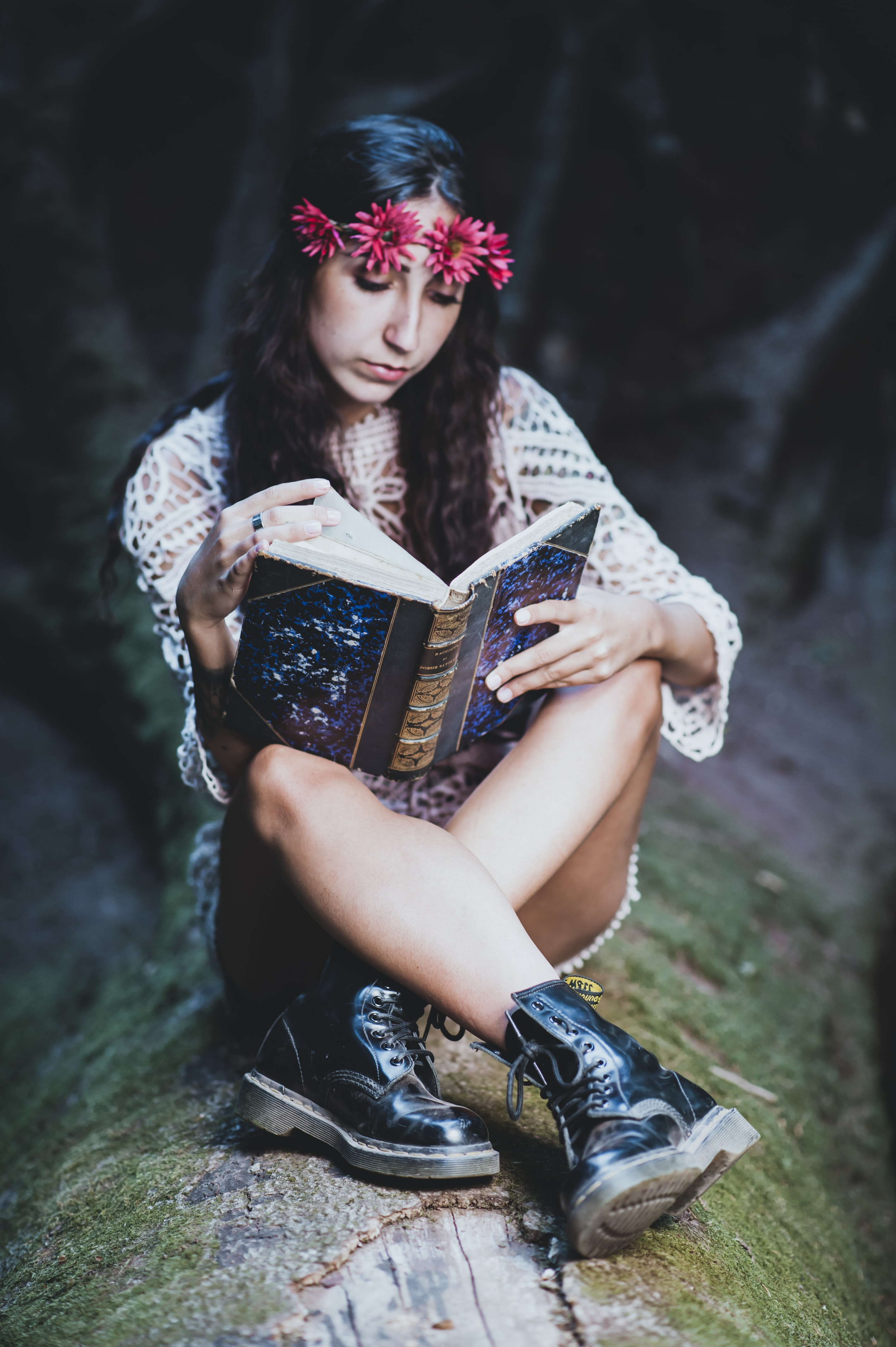 woman wearing white long-sleeved blouse and black leather work boots reading blue and brown book