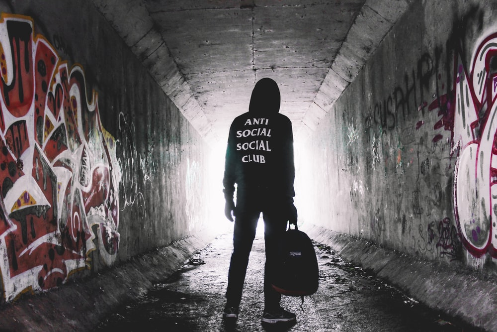person holding bag standing inside tunnel