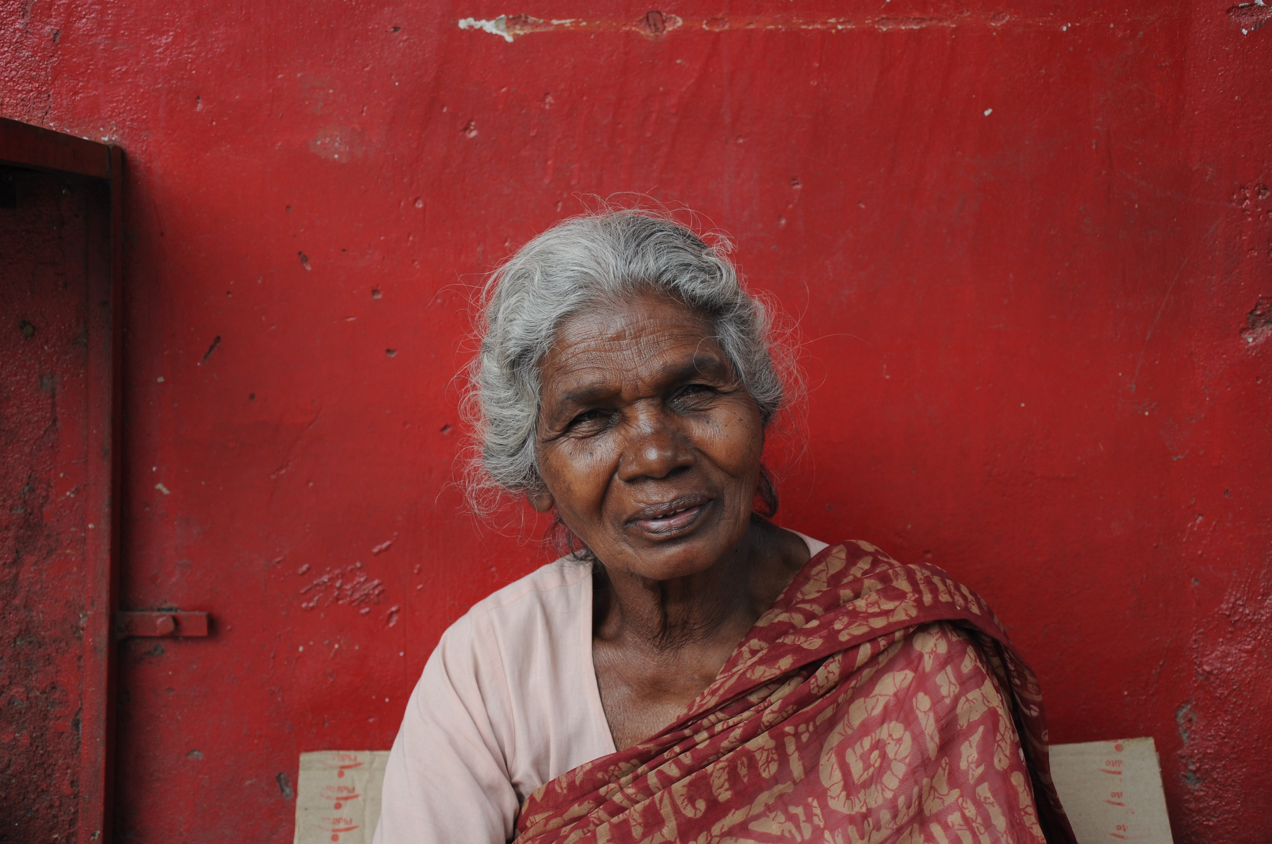 woman sitting near red painted wall