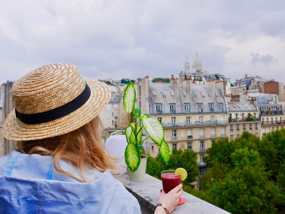 woman holding glass with red juice while in terrace