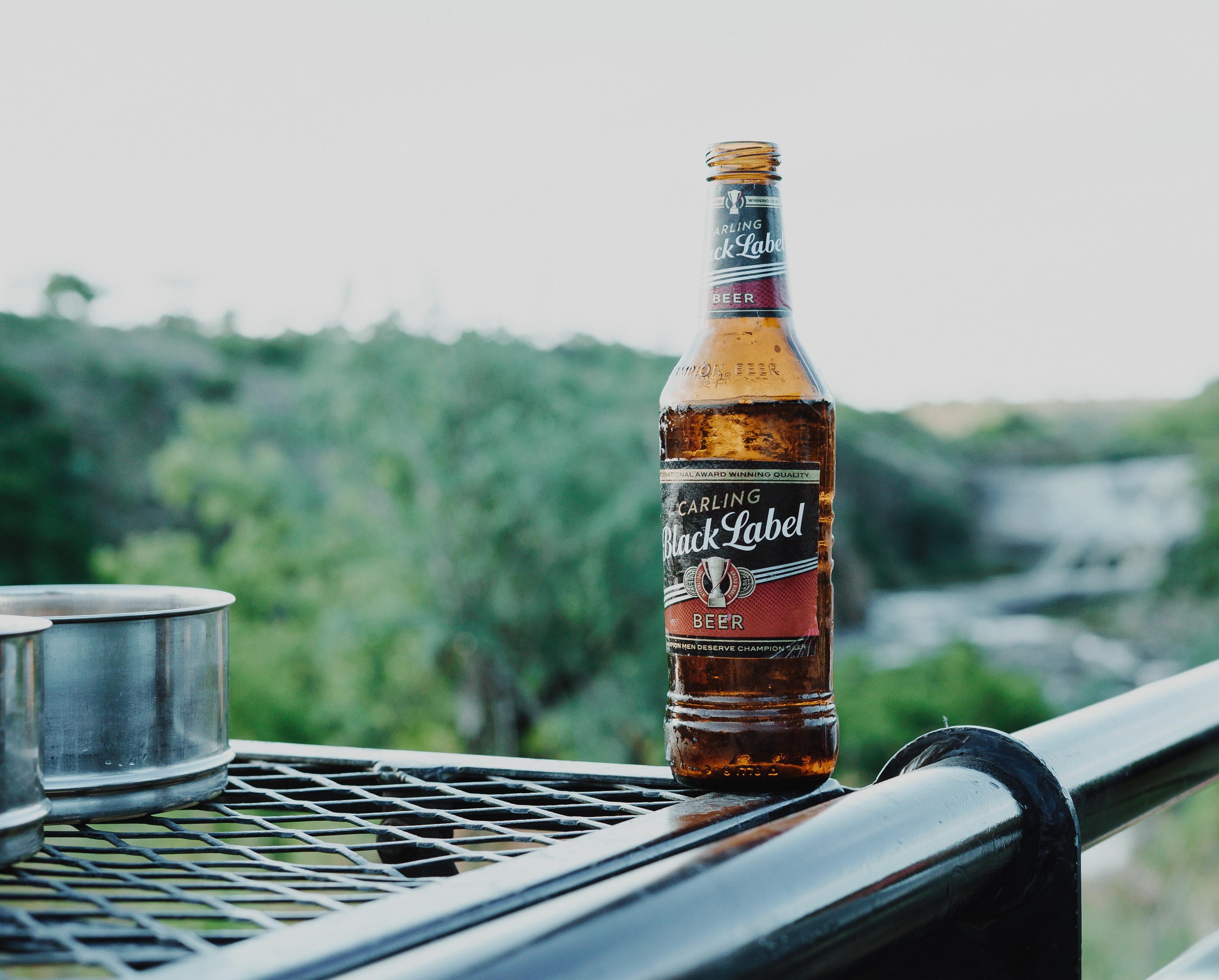 brown glass bottle on grey metal rail