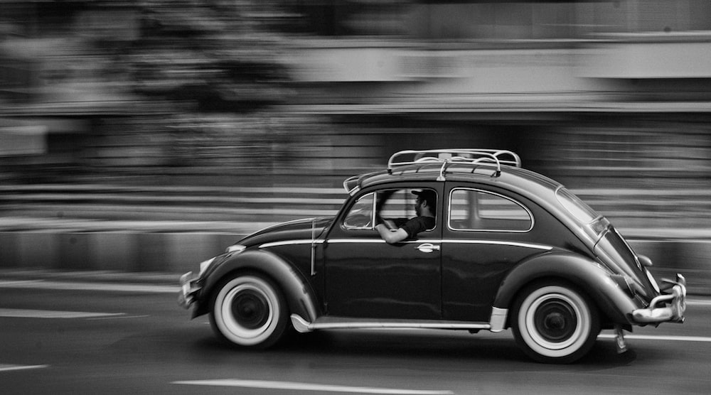 grayscale photo of moving beetle car