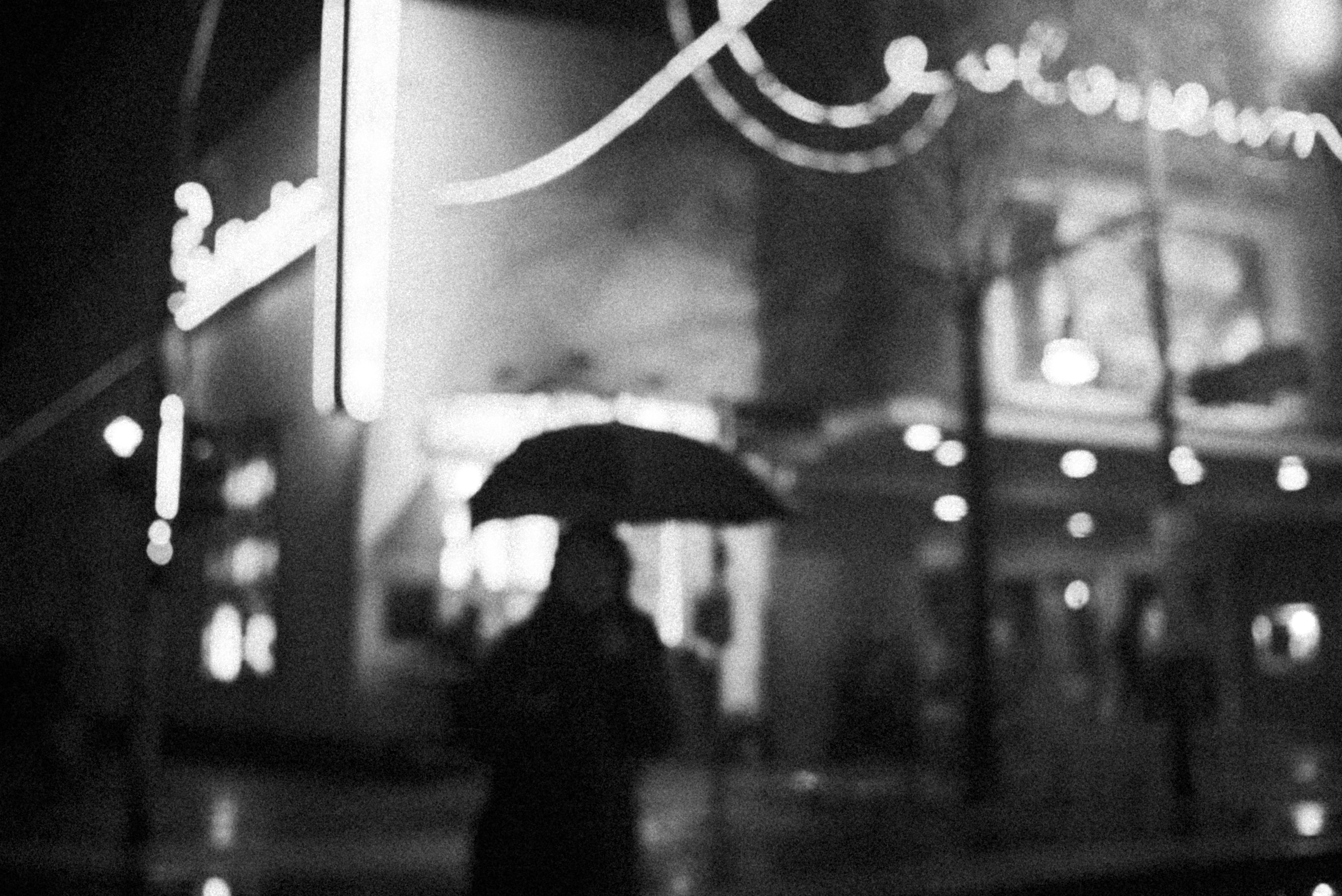 grayscale photo of woman holding umbrella