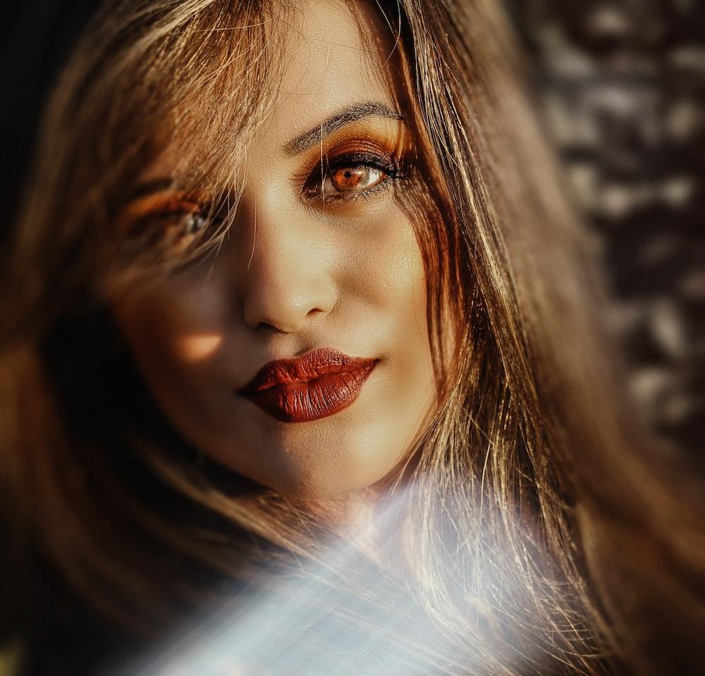 selective photo of woman wearing red matte lipstick