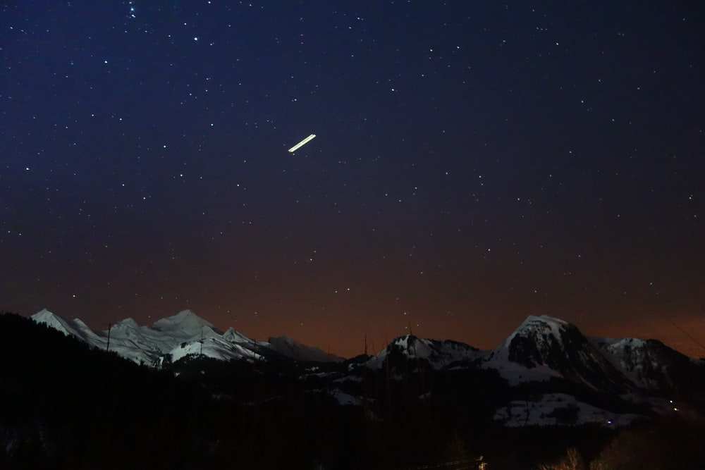 silhouette photo of mountains covered in snow at nighttime
