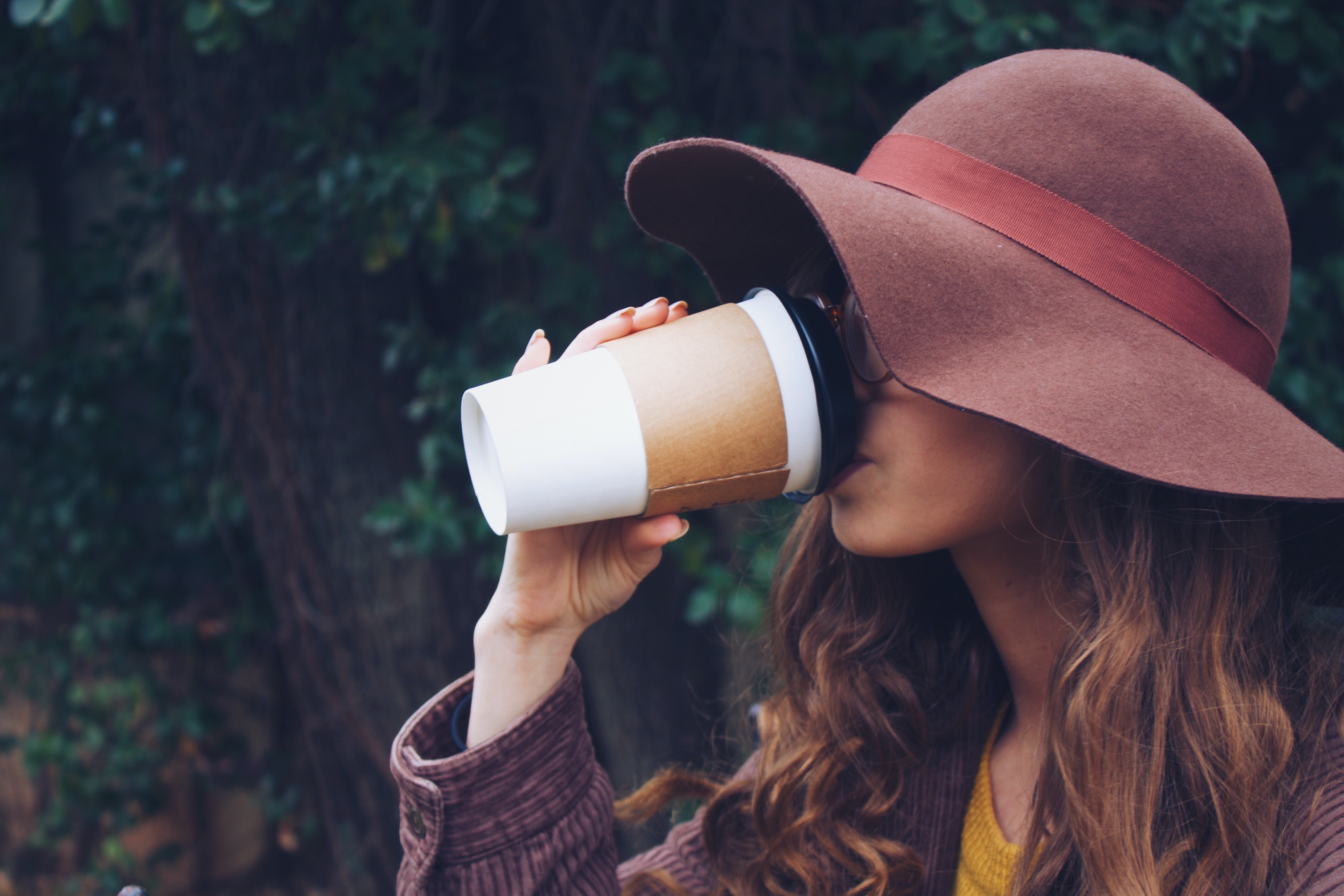 woman wearing brown hat drinking coffee