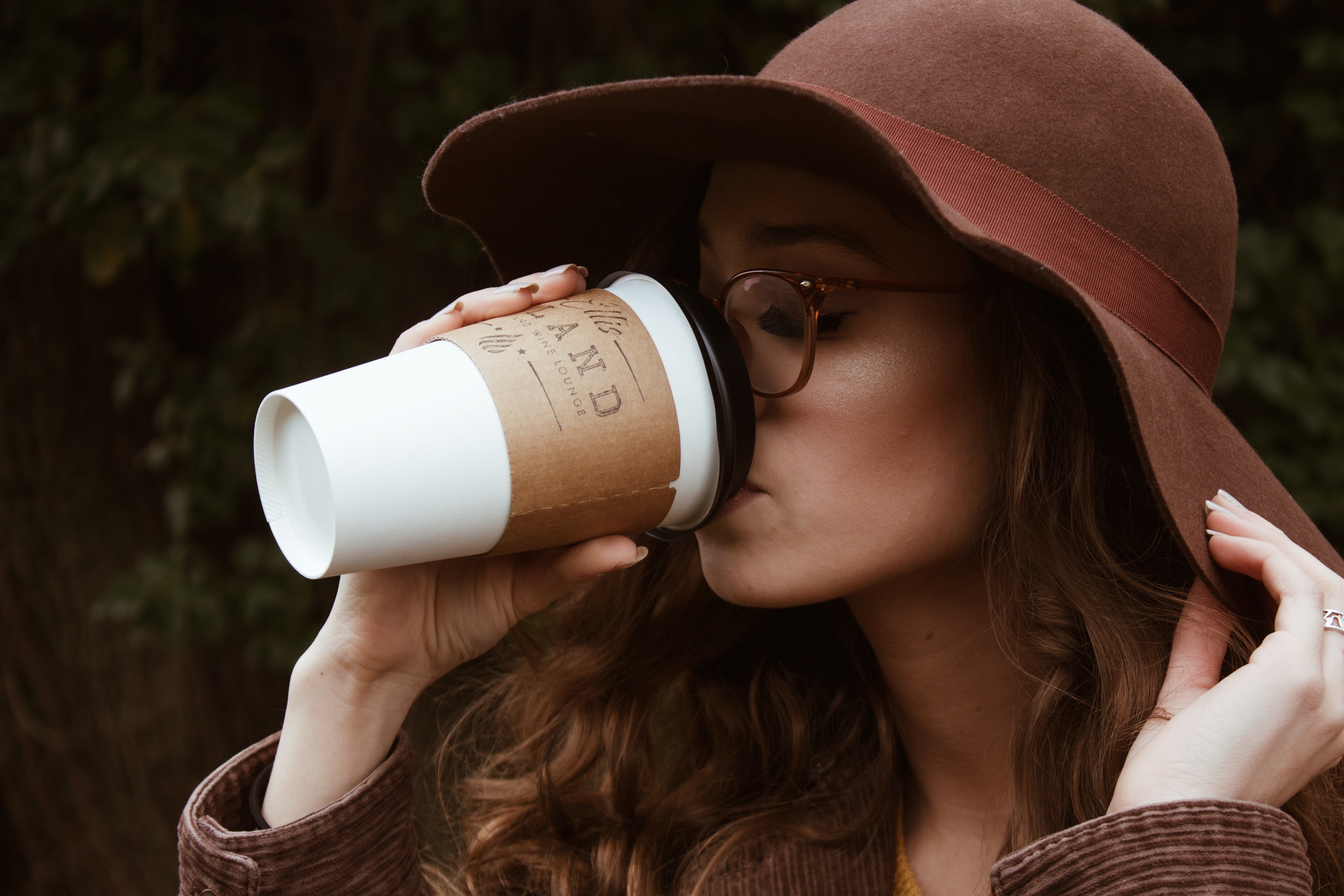 woman with brown hat and tortoiseshell framed eyeglasses drinking coffee in plastic cup