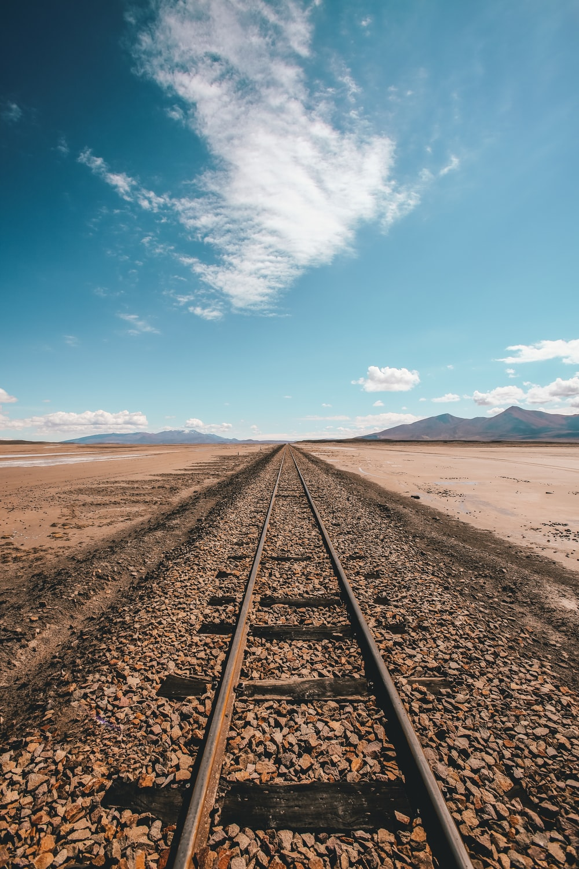 brown train rail in desert under blue and white sky