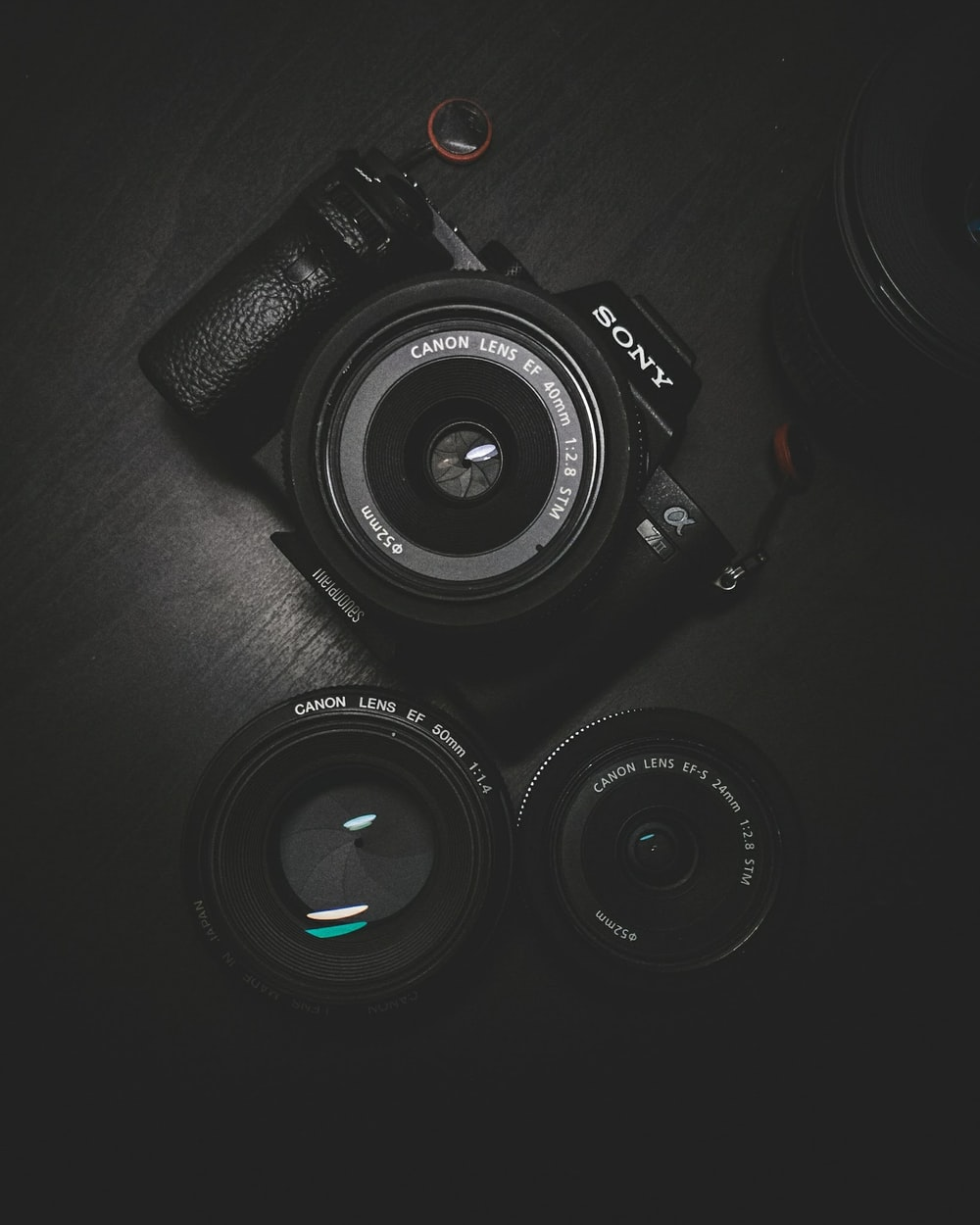 flat lay photography of black Sony DSLR camera on black surface