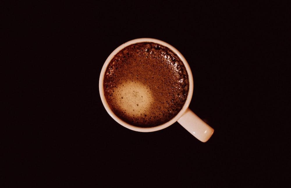 top view of white ceramic mug with brown liquid