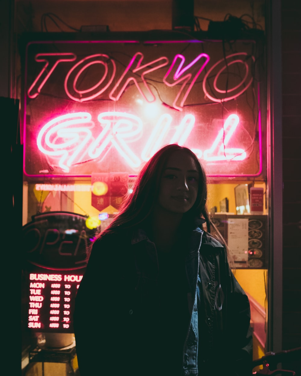 woman standing behind red Tokyo Grill neon signage