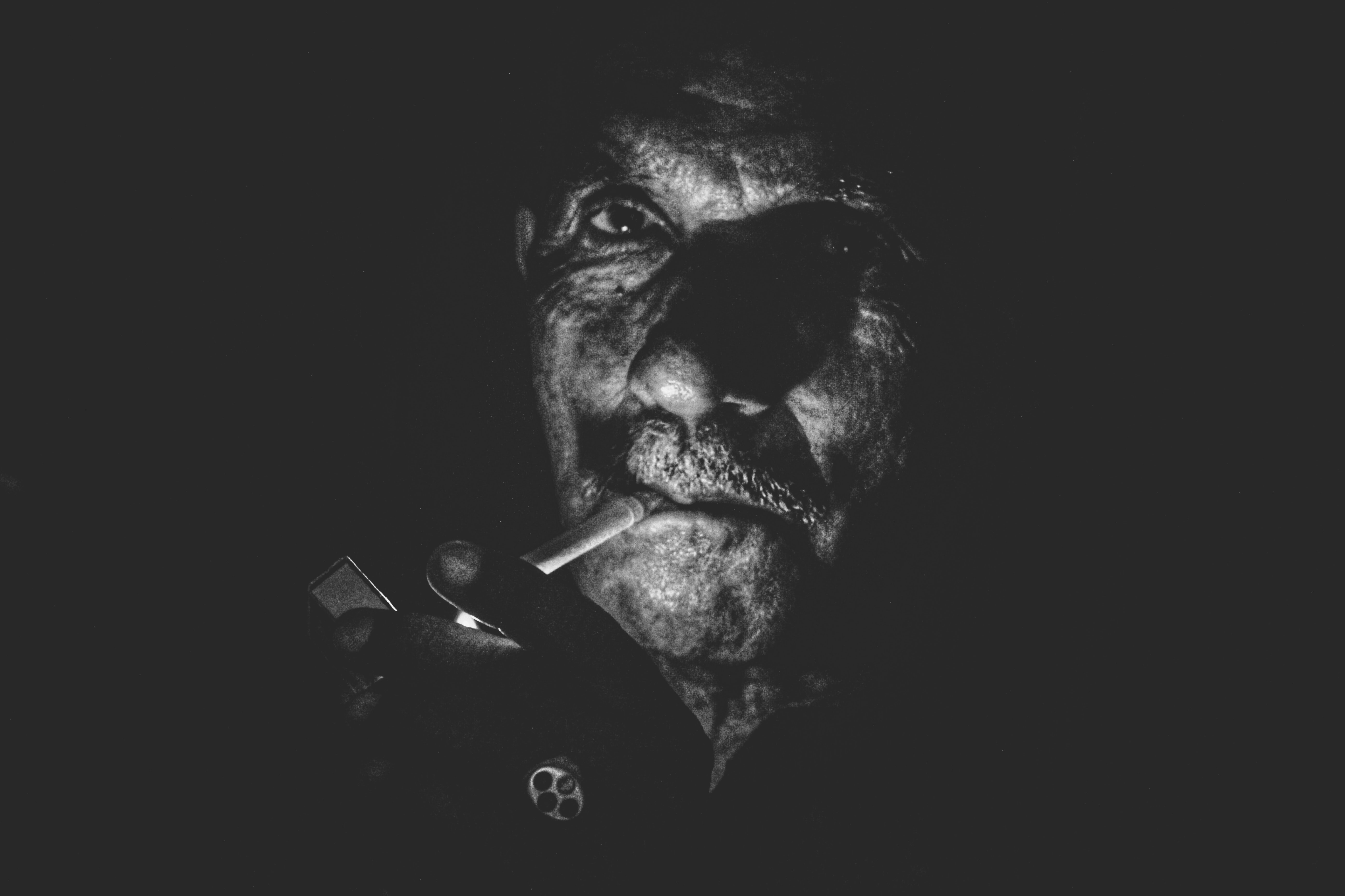 greyscale photo of man lighting cigarette close-up photo
