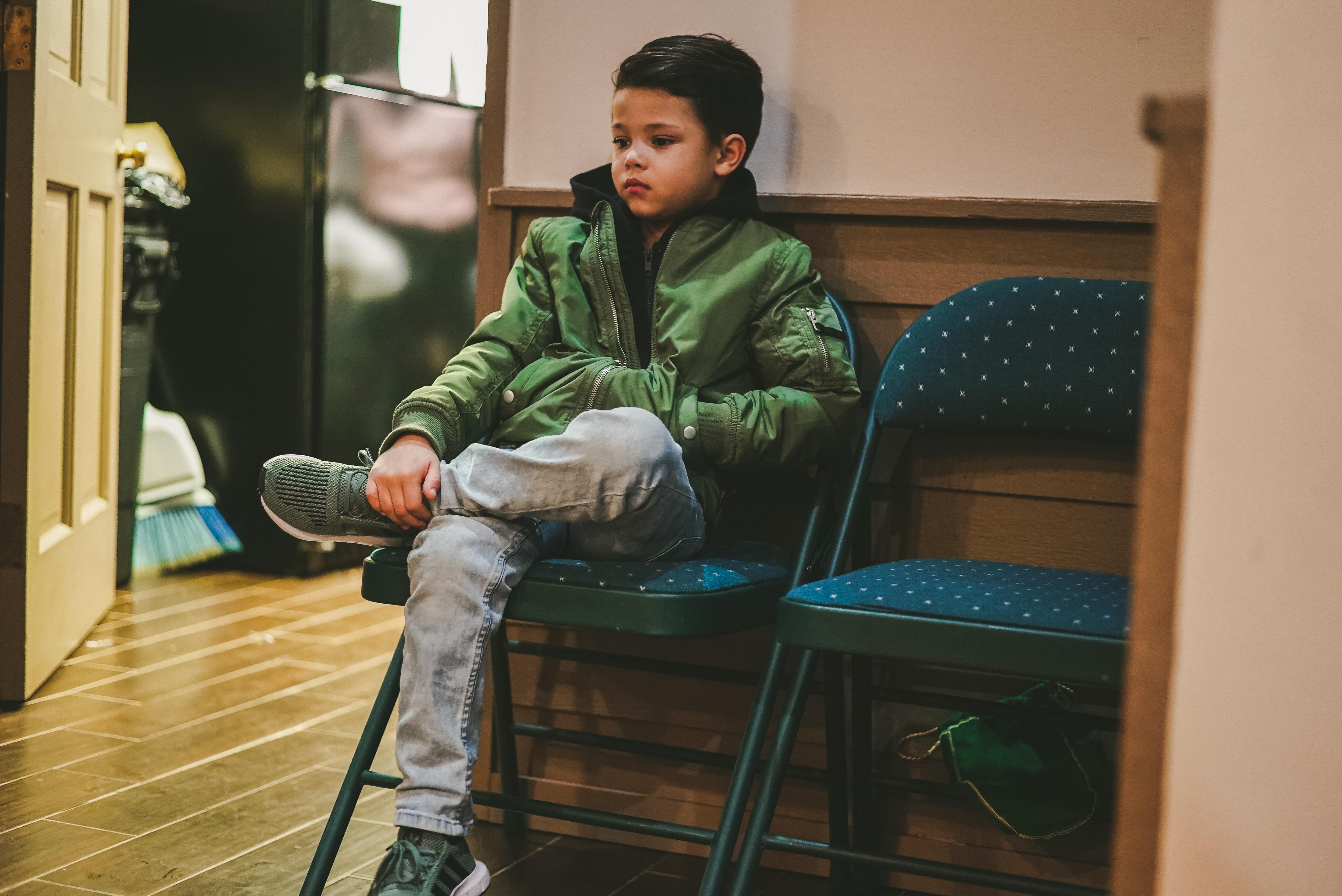 boy in green jacket sits on folding padded chair near door inside room