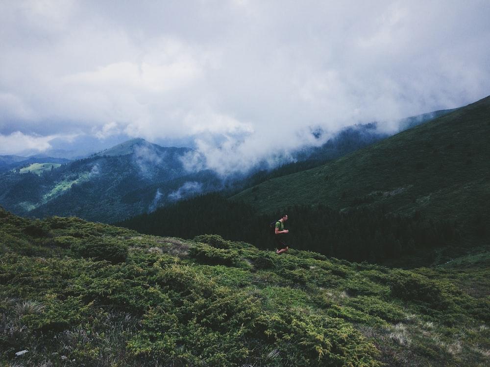 person walking on grass field near mountain