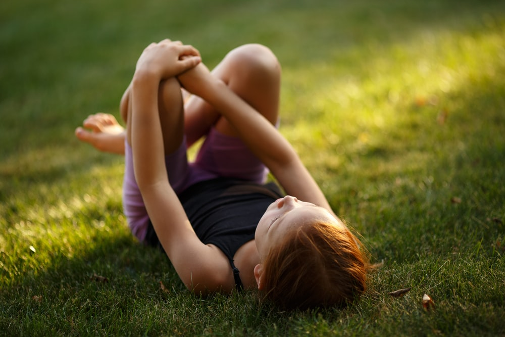 girl lying on green grass