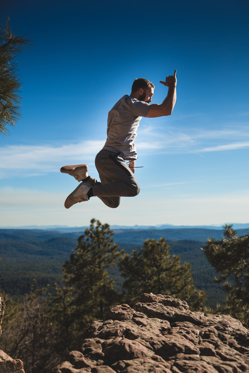 man jumping on brown rock formation