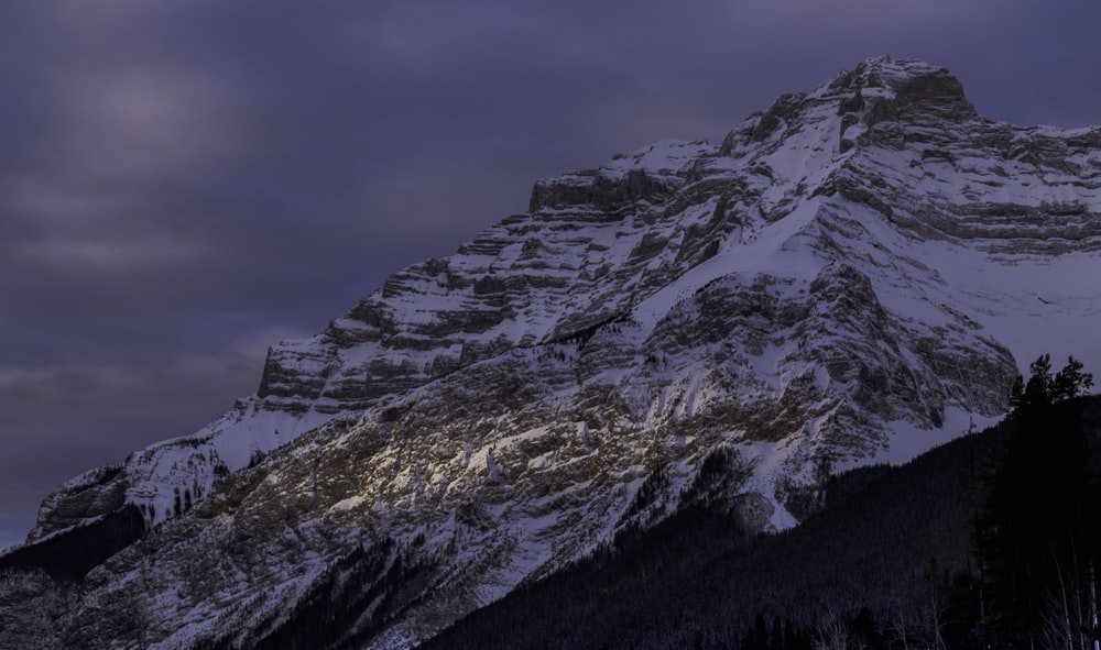 rock mountain covered with snow at daytime