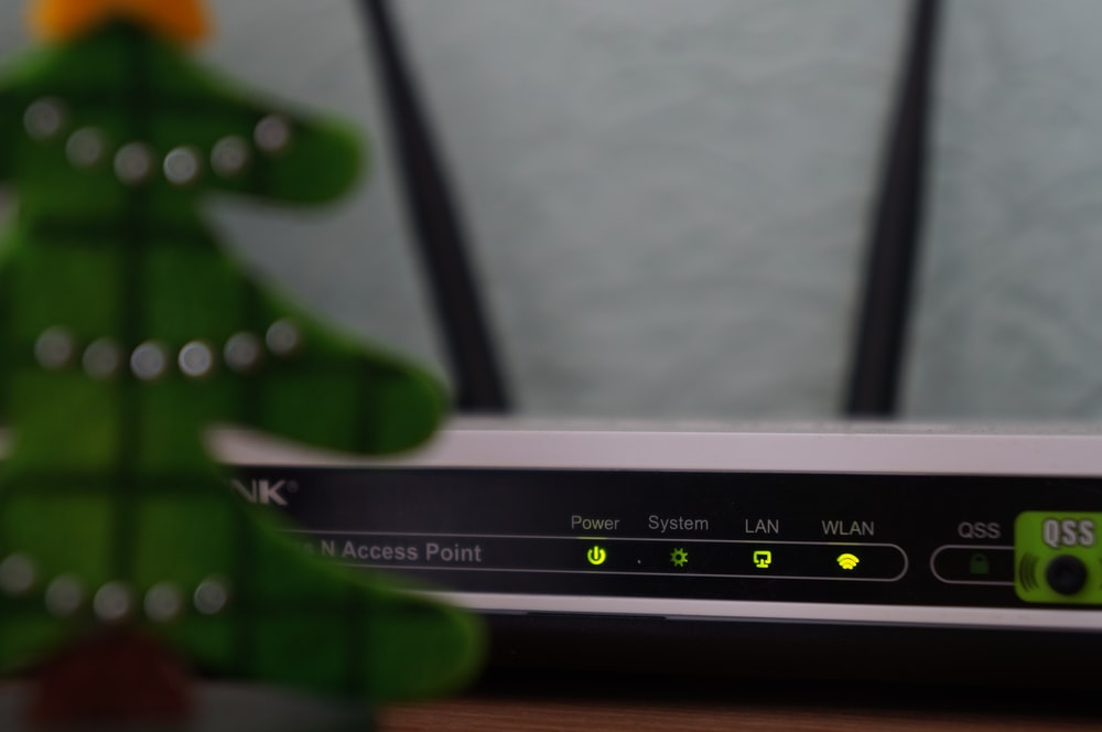 white and black modem router with four lights