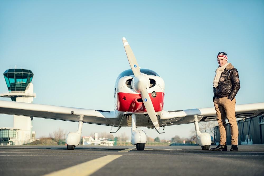 man standing near red biplane