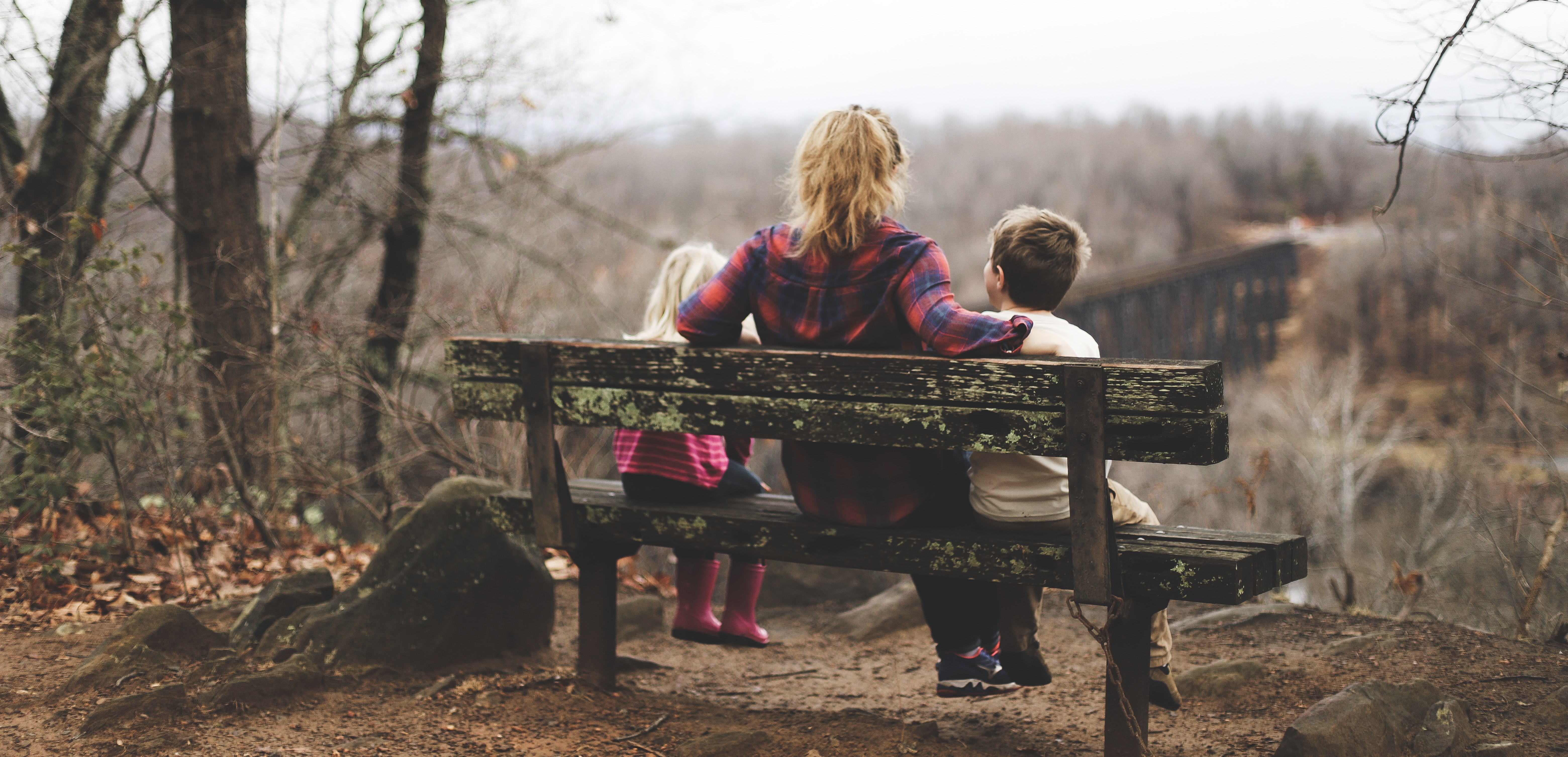 woman between two childrens sitting on brown wooden bench during daytime