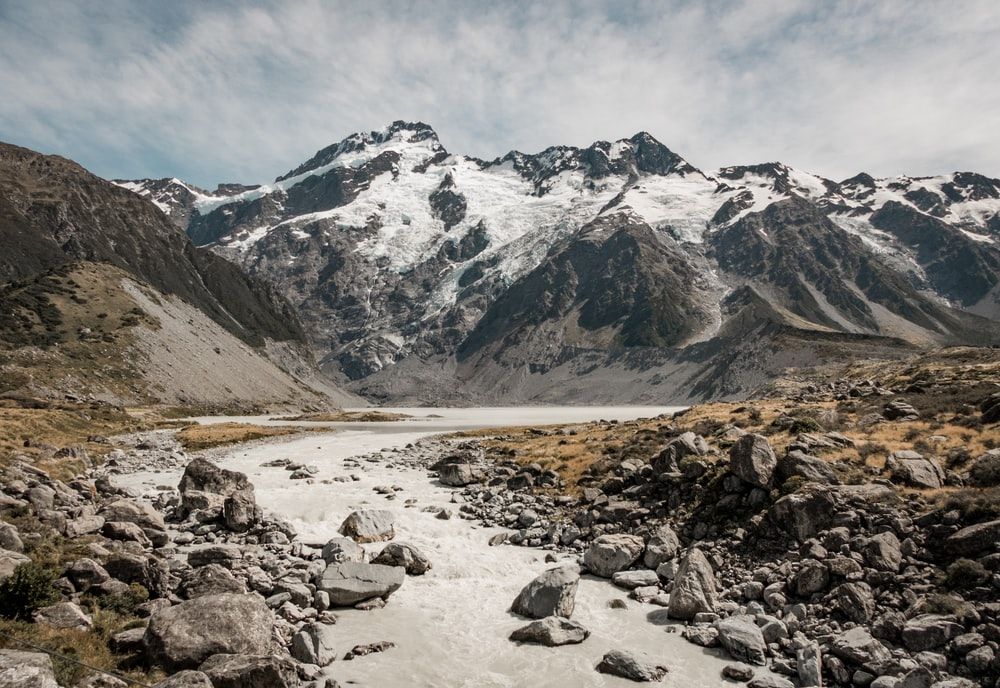 river and rock mountain with snow during daytime