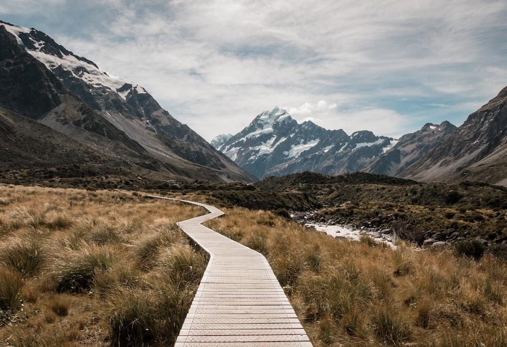 brown wooden dock towards mountain near creek and glacier mountains