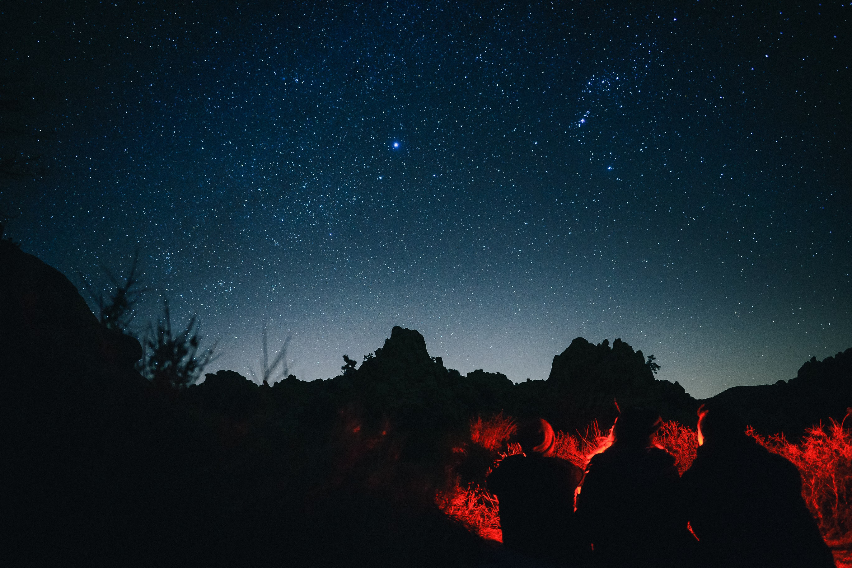 silhouette photo of three person sitting infront of bonfire under night sky