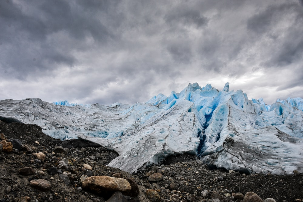 mountain covered with ice under grey cloudy sky