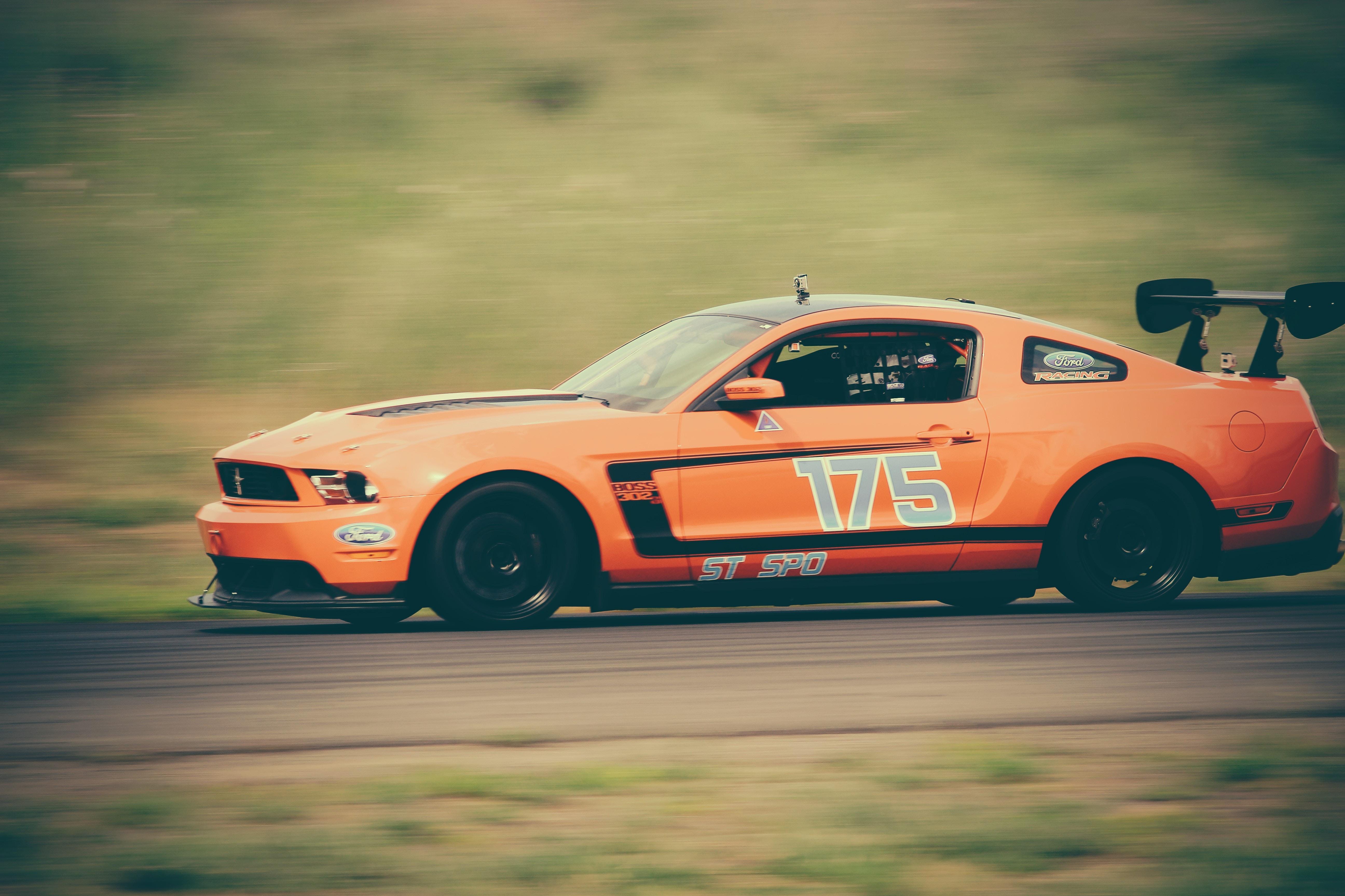 panning photography of orange racing car on road
