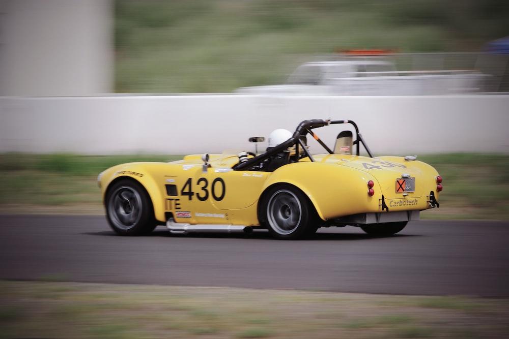 man riding yellow racing car