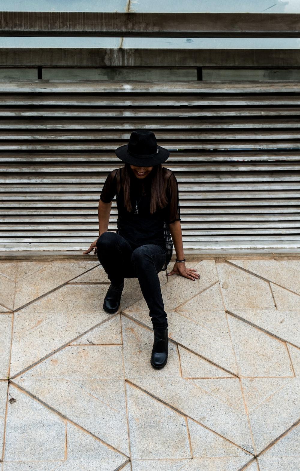 woman in black shirt sitting on gray concrete