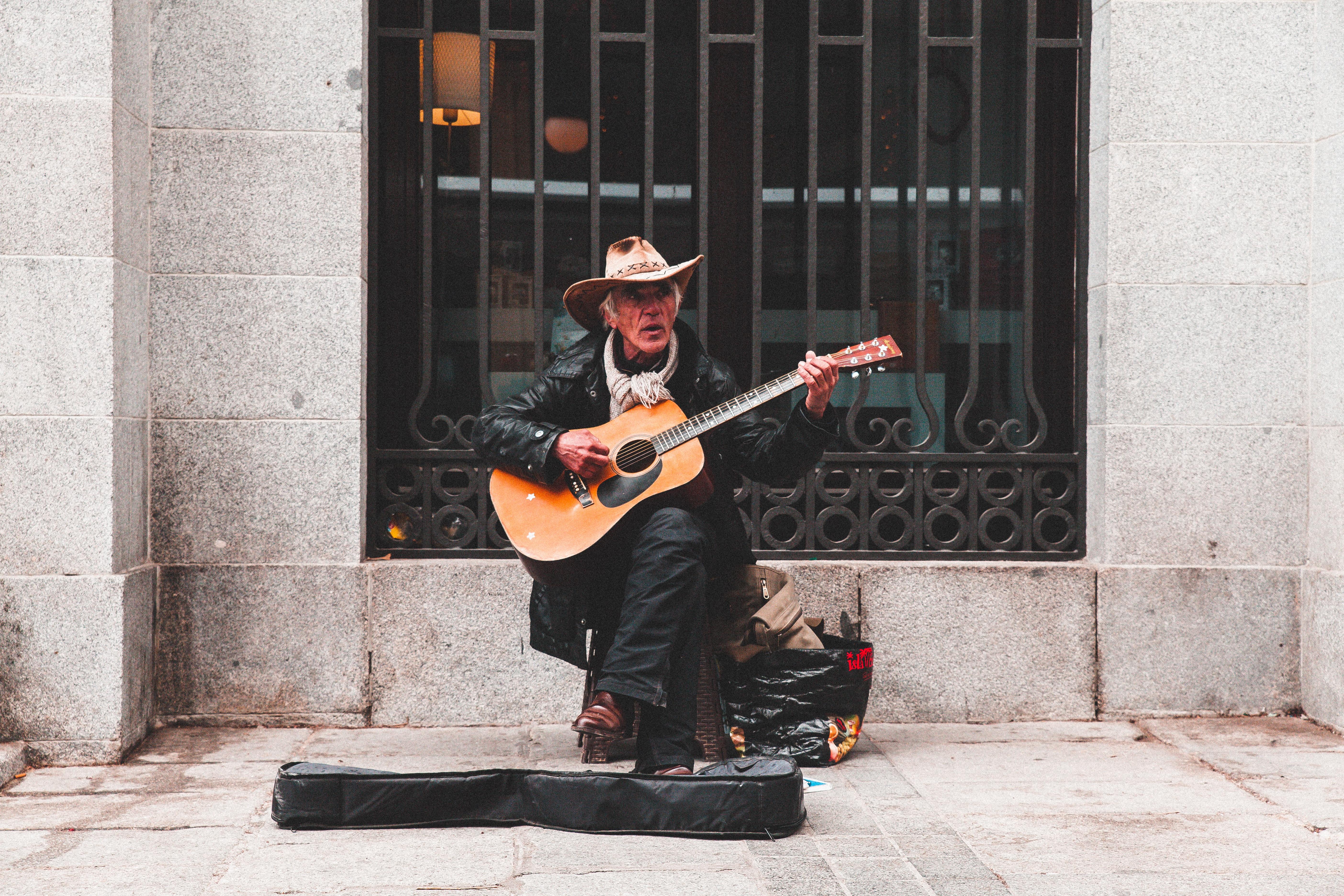 man sitting on chair playing guitar