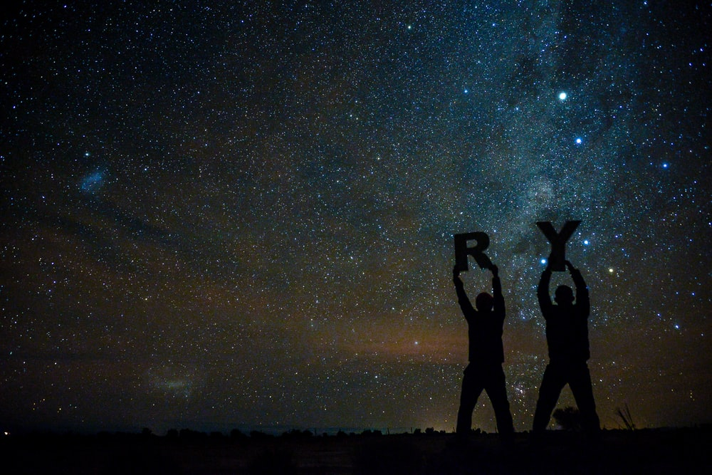 silhouette of two person holding letters R and Y under starry sky