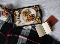 flat-lay photography of food served on plate on top of black wooden serving tray