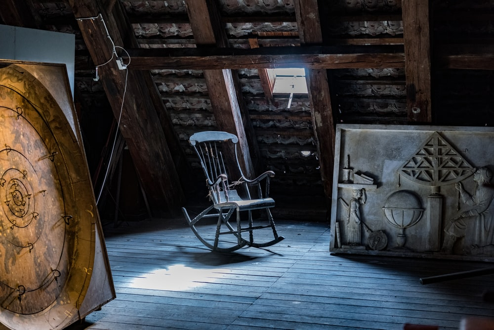 brown wooden rocking chair on brown wooden planks